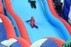 Behandla som ett barn flickan rider och skrikig gyckel på en uppblåsbar glidbana på Royaltyfria Bilder