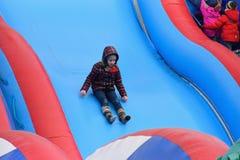 Behandla som ett barn flickan rider och skrikig gyckel på en uppblåsbar glidbana på Fotografering för Bildbyråer