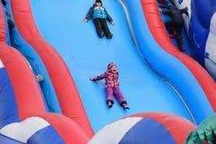 Behandla som ett barn flickan rider och skrikig gyckel på en uppblåsbar glidbana på Royaltyfri Foto