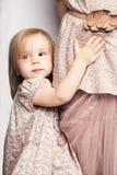 Behandla som ett barn flickan som rymmer hennes moderkjol Barndombegrepp royaltyfri fotografi