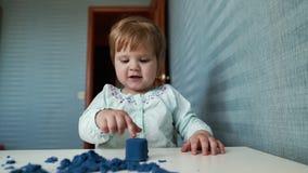 Behandla som ett barn flickan sitter på en childstabell och lekar med kinetisk sand i ultrarapid arkivfilmer