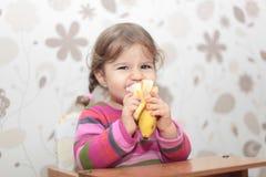Behandla som ett barn flickan som äter bananen Royaltyfri Foto