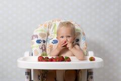 Behandla som ett barn flickan som äter jordgubbar Royaltyfri Fotografi