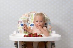 Behandla som ett barn flickan som äter jordgubbar Arkivfoto