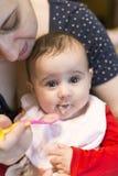 Behandla som ett barn flickan som äter mat för första gång arkivfoto