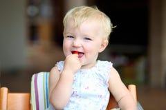 Behandla som ett barn flickan som äter tomater Arkivbilder