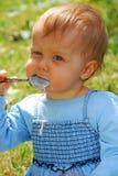 Behandla som ett barn flickan som äter vid hon själv utomhus- Royaltyfri Bild