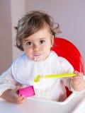 Behandla som ett barn flickan som äter yoghurt med den smutsiga framsidan Arkivbild
