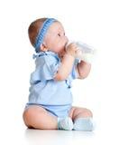 Behandla som ett barn flickan som att dricka mjölkar från bottlee utan hjälp Fotografering för Bildbyråer