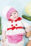 Behandla som ett barn flickan som bär en kockhatt med grönsaker Royaltyfri Bild