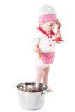Behandla som ett barn flickan som bär en kockhatt med grönsaker och pannan som isoleras på vit bakgrund. Arkivbilder