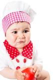 Behandla som ett barn flickan som bär en kockhatt med tomaten som isoleras på vit bakgrund. Royaltyfri Fotografi