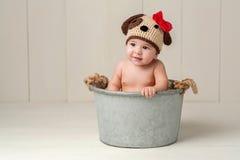 Behandla som ett barn flickan som bär en virkad hatt för valphund royaltyfri foto