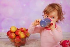 Behandla som ett barn flickan som dricker en äppelmust Arkivfoto