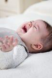 Behandla som ett barn flickan som gråter över den vita sängöverkastet Arkivfoton