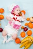 Behandla som ett barn flickan som ha på sig en kockhatt med frukter Fotografering för Bildbyråer