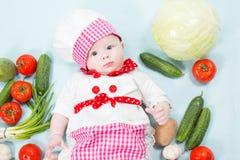 Behandla som ett barn flickan som ha på sig en kockhatt med grönsaker Royaltyfria Foton