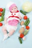Behandla som ett barn flickan som ha på sig en kockhatt med grönsaker Arkivbild