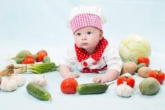 Behandla som ett barn flickan som ha på sig en kockhatt med grönsaker Fotografering för Bildbyråer