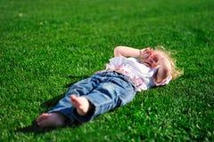 Behandla som ett barn flickan som lägger på det gröna gräset i parkera Royaltyfri Bild