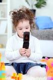 Behandla som ett barn flickan som leker med den mobila telefonen Royaltyfria Bilder