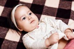 Behandla som ett barn flickan som ligger på den rutiga plädet Arkivfoto
