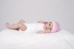 Behandla som ett barn flickan som ligger på säng Royaltyfri Foto