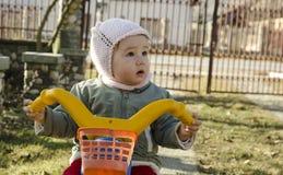 Behandla som ett barn flickan som rider hennes cykel Arkivbild