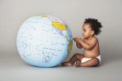 Behandla som ett barn flickan som ser det uppblåsbara jordklotet Arkivbilder