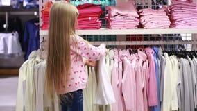 Behandla som ett barn flickan som ser kläder i innegrej, shoppar stock video
