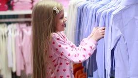 Behandla som ett barn flickan som ser kläder i innegrej, shoppar lager videofilmer
