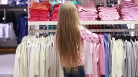 Behandla som ett barn flickan som ser kläder i innegrej, shoppar arkivfilmer