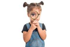 Behandla som ett barn flickan som ser till och med ett förstoringsglas Royaltyfria Bilder