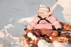 Behandla som ett barn flickan som sitter på snow Fotografering för Bildbyråer