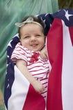 Behandla som ett barn flickan som slås in i amerikanska flaggan Arkivbild