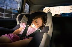 Behandla som ett barn flickan som sover i bilen Royaltyfri Bild