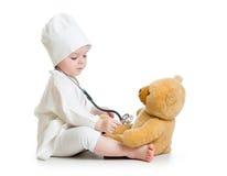 Behandla som ett barn flickan som spelar doktorn med nallebjörnen Fotografering för Bildbyråer