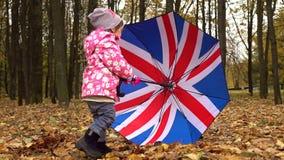 Behandla som ett barn flickan som spelar med britt flagga-som paraplyet i höst, parkerar Dåligt väderbegrepp skott för steadicam  stock video