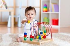 Behandla som ett barn flickan som spelar med den bildande leksaken i barnkammare Arkivbild