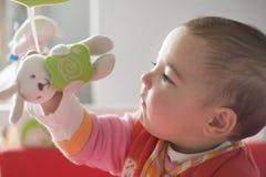 Behandla som ett barn flickan som spelar med henne, behandla som ett barn den musikaliska mobila leksaken Royaltyfri Bild