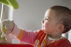 Behandla som ett barn flickan som spelar med henne, behandla som ett barn den musikaliska mobila leksaken Arkivbild