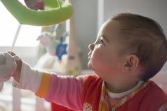 Behandla som ett barn flickan som spelar med henne, behandla som ett barn den musikaliska mobila leksaken Royaltyfri Fotografi
