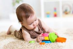 Behandla som ett barn flickan som spelar med inomhus leksaker Fotografering för Bildbyråer