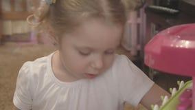 Behandla som ett barn flickan som spelar med leksaker i lekrummet lager videofilmer