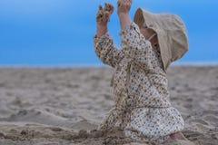 Behandla som ett barn flickan som spelar med sand på stranden Arkivfoto