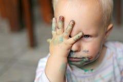 Behandla som ett barn flickan som täcker den smutsiga framsidan med små händer Royaltyfria Bilder
