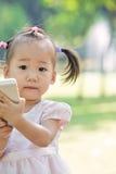 Behandla som ett barn flickan som tar fotoet vid mobil 2 Fotografering för Bildbyråer