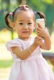 Behandla som ett barn flickan som tar fotoet vid mobilen Royaltyfri Fotografi