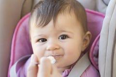 Behandla som ett barn flickan som äter yoghurt Royaltyfri Fotografi