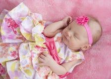 Behandla som ett barn flickan som sover i blom- klänning Royaltyfria Foton